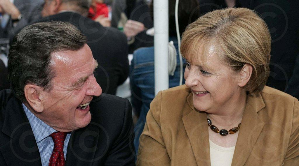 German Chancellor Merkel (CDU) and her predecessor Schroeder (SPD) laughing / @ Berlin